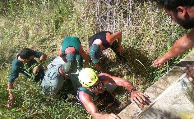 Un grupo de guardias civiles rescatan el cadáver del menor.