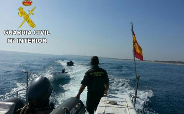 Una embarcación de la Guardia Civil remolca la patera. / Guardia Civil