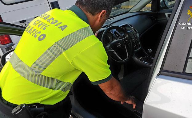 Agente de la Guardia Civil de Tráfico comprobando el cuenta kilómetros de uno de los vehículos.