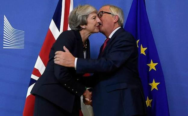 Jean-Claude Juncker saluda, ayer, a Theresa May.
