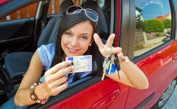 Una joven muestra su carnet de conducir.