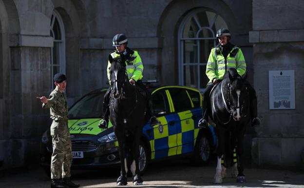 Dos oficiales de polícia hablan con un miembro del Ejército británico en Londres