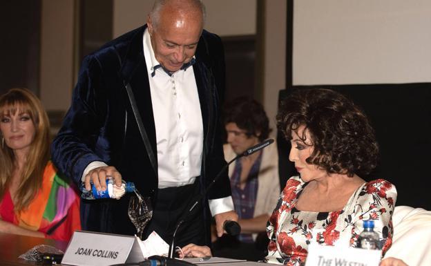 José Luis Moreno, llena la copa de Joan Collins de agua.