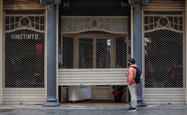 Un trabajador baja la persiana de un comercio de hostelería en Valencia. /efe/biel aliño