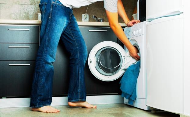 Un hombre instala una lavadora.  / lp