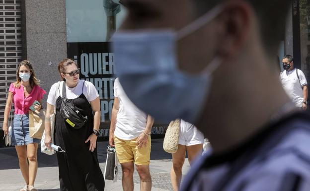 Varias personas con máscaras en una foto de archivo./IVÁN ARLANDIS